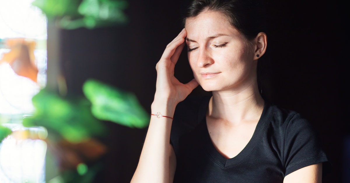 A woman is experiencing a light-sensitivity headache