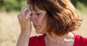 A woman is pinching her nose bridge