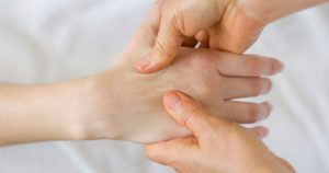 A acupressure doctor is applying pressure to a patient's hand