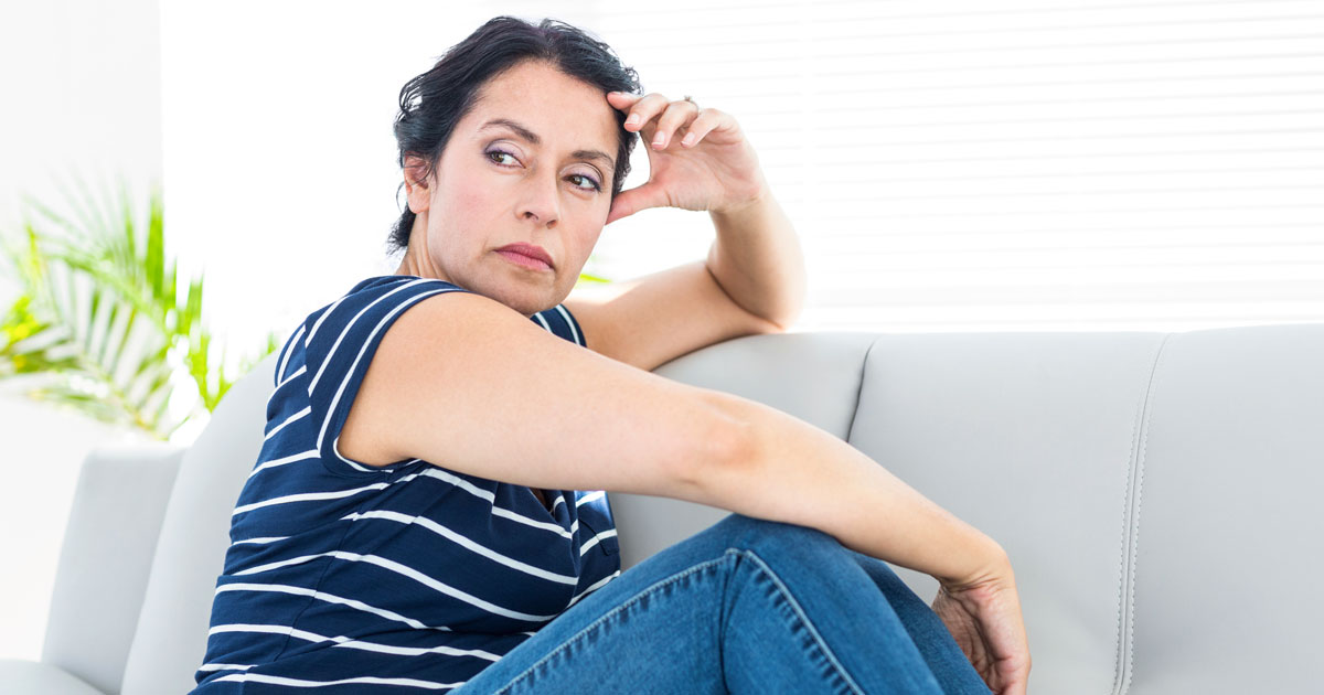 A woman is anxious, while sitting on a couch