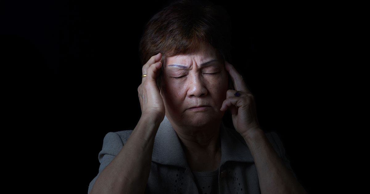 A mature woman is experiencing migraine pain