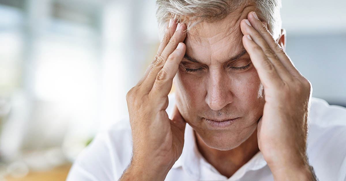 Mature man suffering with a headache
