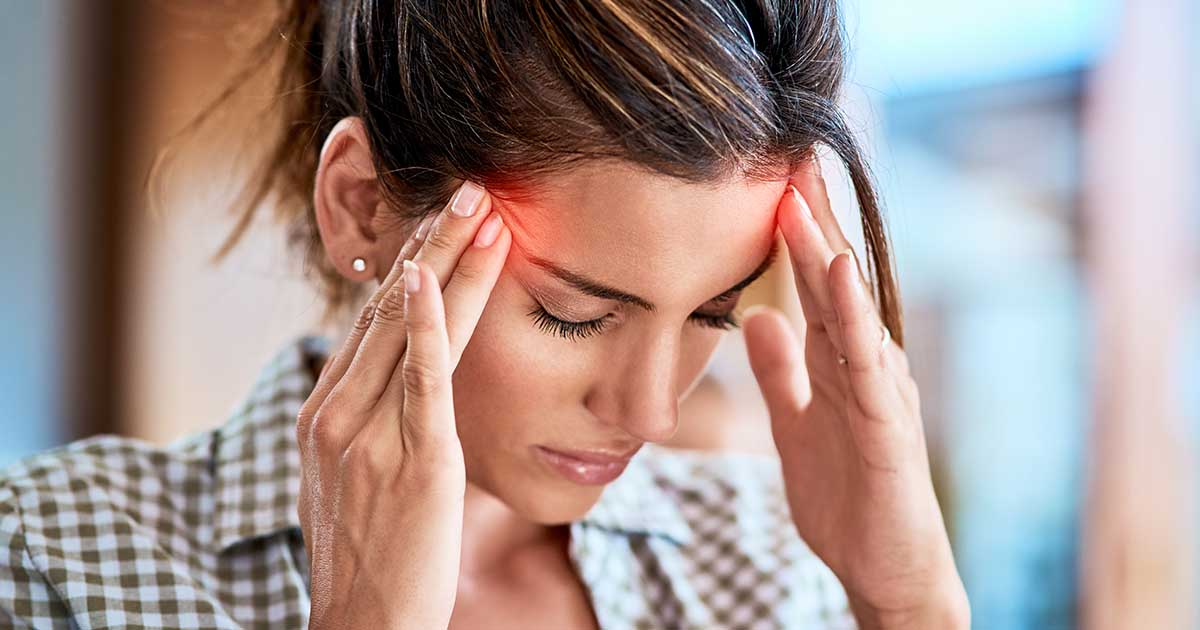 Woman holding her head in discomfort due to pain