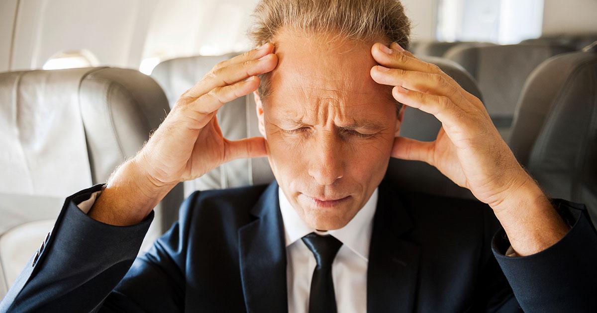 A man is experiencing a headache while in an airplane