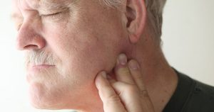 A mature man is experiencing jaw pain