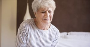 An elderly woman is experiencing pain
