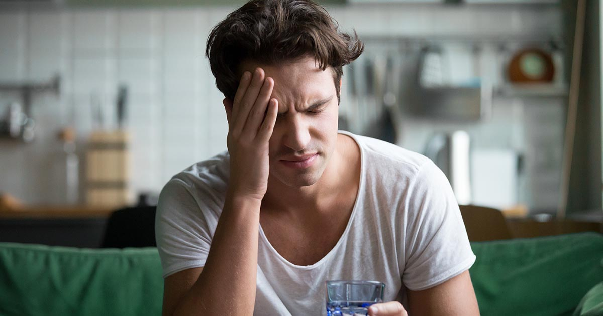Young man suffering from headache or migraine at home