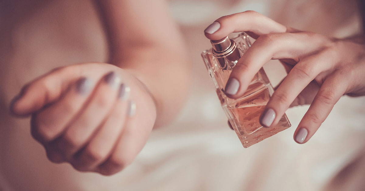 A woman is spritzing perfume on their wrist