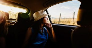 A woman is looking out the backseat car window