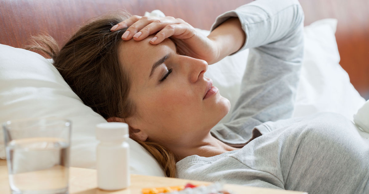 A woman is lying in bed with a headache, on her nightstand are some medications