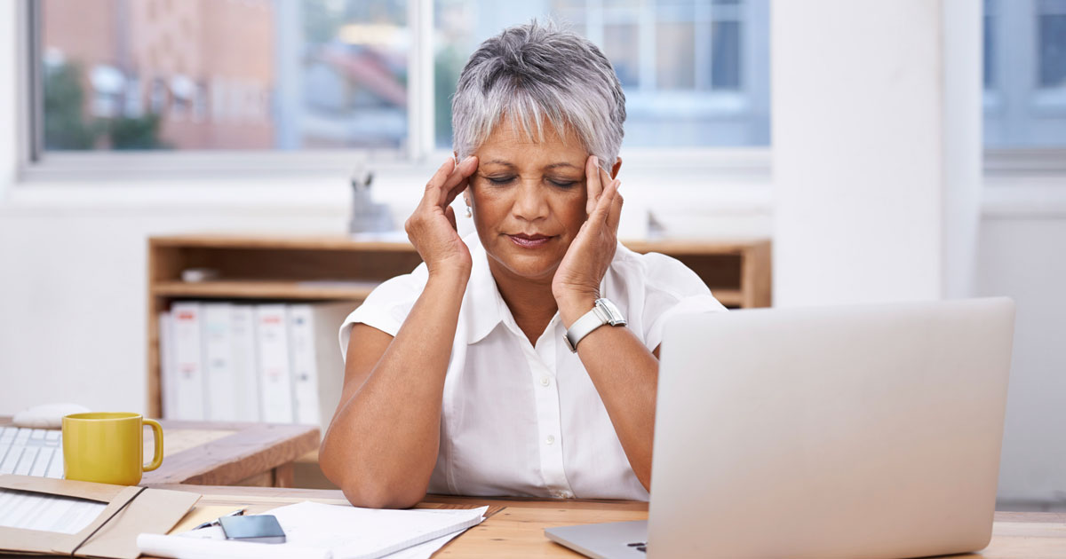 A woman is experiencing a headache at work