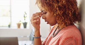 A woman is pinching her nose bridge