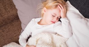 A child is experiencing a headache, while laying in bed