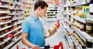 Man is reading nutritional label of a product at a grocery store