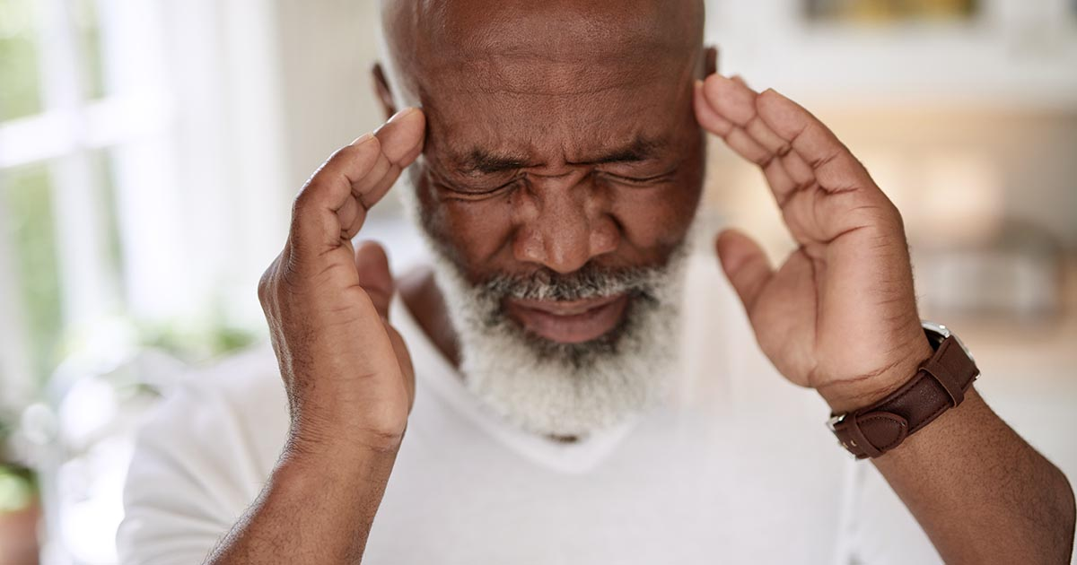 A man is experiencing a painful migraine
