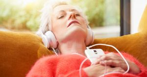 an older woman listening to some migraine relief music while lying down on a couch