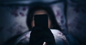 A person laying in bed on their phone.